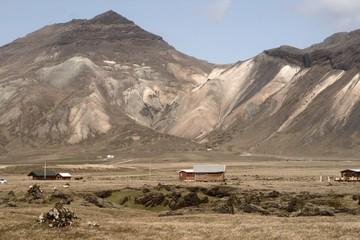 Mehrfarbiger sandiger Hang mit Hütte im Vordergrund