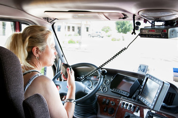Blonde woman truck driver talking on her radio.
