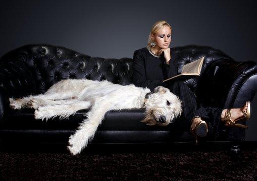 junge Frau mit Hund liest Buch