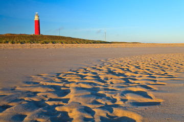 Seaside with sand dunes and lighthouse at sunset Wall mural