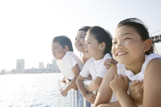 船上から外を見る母と子供たち