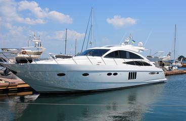 white yacht mooring in marina