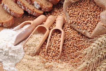Wood spoons with whole wheat grains, wheat bran and flour