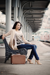 Girl with a suitcase sitting on the ramp