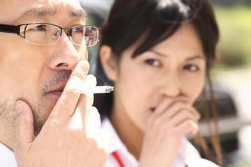 Fototapeta タバコを吸うビジネスマンと嫌がるオフィスレディ obraz
