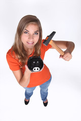 Teenage girl holding piggy bank and hammer