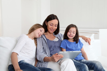 Mother and girls using electronic tablet at home