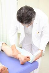 患者の足にシーネを取り付ける医者