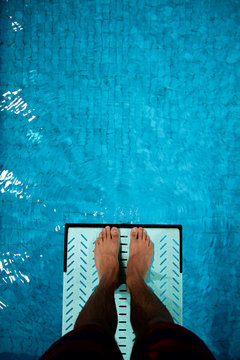 feet on diving board over pool