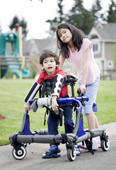 Big sister helping younger disabled brother in walker