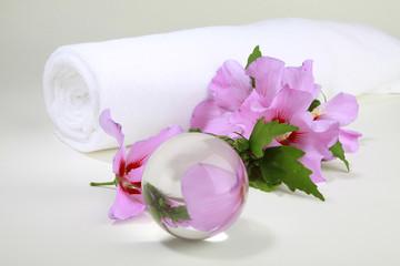 Hibiskusblüten mit weißem Handtuch und Glaskugel