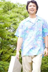 公園を歩くアロハシャツ姿のビジネスマン