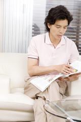ソファーに座り雑誌を読む男