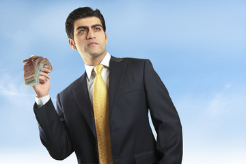 Business man holding money with blue sky background