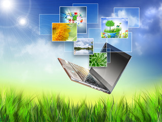 Multimedia concept with modern laptop on green field