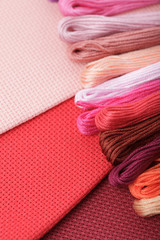 Close up of embroidery canvas, colour floss in warm tones