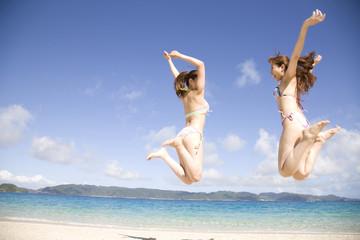浜辺でジャンプする水着を着た2人の女性の後ろ姿