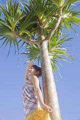 晴天の中椰子の木に寄りかかり太陽の眩しさに手をかざす女性