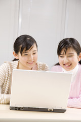ノートパソコンを見る2人の女の子