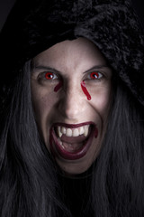 Cloaked vampire, black background.