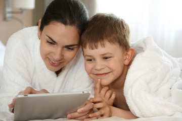 Mother and son using tablet smiling