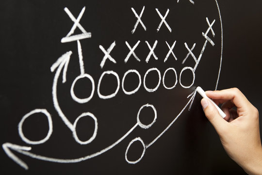 Coach Drawing American Football Game Tactics On Blackboard