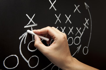 Coach Drawing American Football Game Strategy On Blackboard