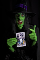 Wicked witch and tarot card, black background.