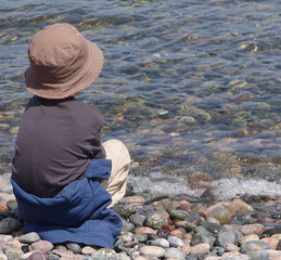 adorable little boy sitting on a rocky beach watching the waves