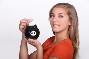 Teenager placing money in piggy bank