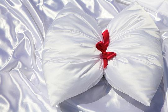 Fiocco rosso su cuscino di seta