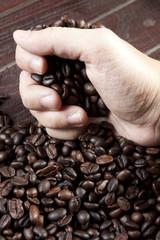 grab beans, a hand grabbing coffee beans.