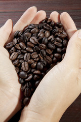 handful coffee bean, female hand scoop up coffee bean.