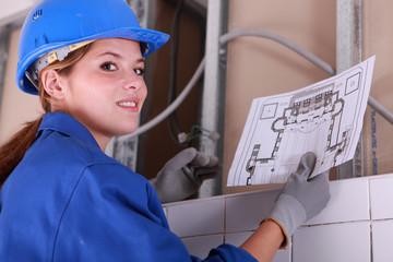 Brunette electrician holding diagram