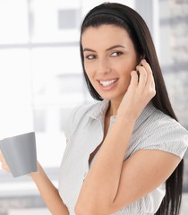 Happy woman on phone call with coffee