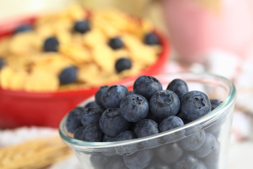 Blueberries in glass bowl with cereal and yogurt