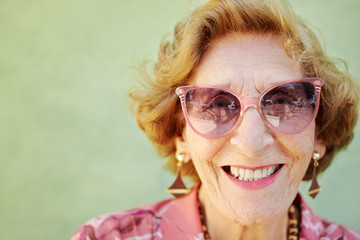 aged woman with pink eyeglasses smiling at camera