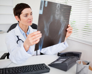 Young female doctor looking at X-ray