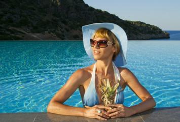 Beautiful woman in the swimminp pool near coast