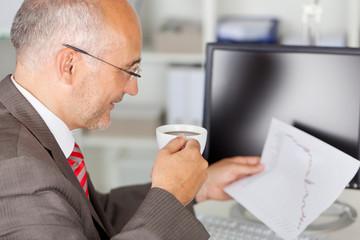 entspannter geschäftsmann mit kaffee am schreibtisch
