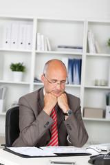 manager mit geschlossenen augen am schreibtisch