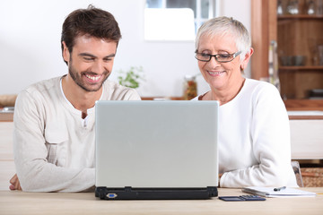 Young man and his mother using laptop