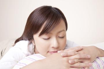 クッションを枕にして眠る女性