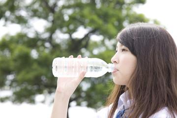 ペットボトルの水を飲む女子高生