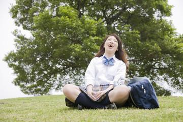 丘に座るペットボトルを持った女子高生