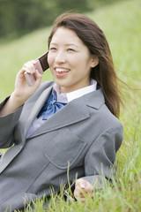 丘に座って携帯電話で話す女子高生
