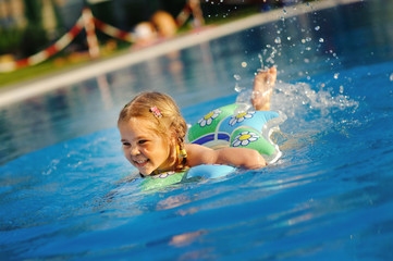 smiling toddler girl swimming in outdoor pool