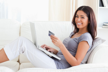 young woman smiling into camera with creditcard in hands