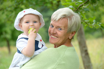 Child on grandmothers arm eating an apple