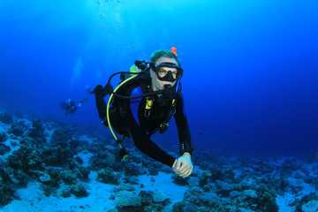 Scuba Diving over coral reef in the clear waters of the Red Sea
